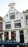 foto van Hoge tuitgevel met rollaag voor huis van parterre, verdieping en zolderverdieping. Sierankers. Stoep met stoeppalen