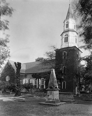 John Page (Middle Plantation) - Bruton Parish Church, Williamsburg, Virginia. Original church built 1683 on land donated by Colonel John Page. The shaft commemorating Col. Page is at right of the church door in this photograph by Frances Benjamin Johnston.