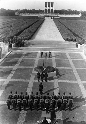 Nuremberg Rally - The Totenehrung (honoring of the dead) at the 1934 Nuremberg Rally. SS leader Heinrich Himmler, Adolf Hitler and SA leader Viktor Lutze (from L to R) on the stone terrace in front of the Ehrenhalle (Hall of Honor) in the Luitpoldarena. In the background is the crescent-shaped Ehrentribüne (the Tribune of Honor).