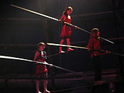 Two tightrope walkers with balance poles support a third who stands on a bar supported by the initial two walkers' shoulders.