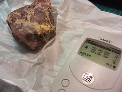 Carnotite with a geiger counter.jpg