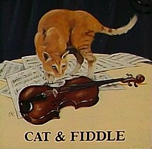 Cat standing on a table with a fiddle and sheet music, from pub sign as seen in 2009