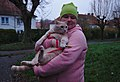 Cat in a harness being held by a pink human and holding a leaf in Auderghem, Belgium.jpg