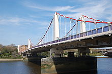Suspension bridge crossing a wide river, under blue skies with clouds. The main cables are red and the towers white.