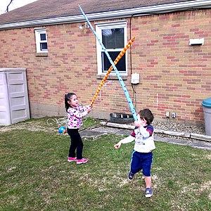 Make believe - Children pretend to play a lightsaber combat.