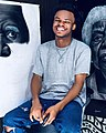 Cookey Ibim posing for a smile in front of his original pieces.jpg