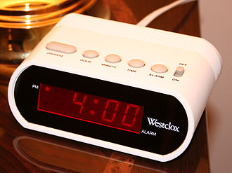 12-hour clock - Typical digital 12-hour alarm clock indicating p.m. with a dot to the left of the hour