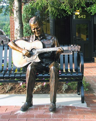 "Doc Watson - Doc Watson sculpture on the corner of King and Depot Streets in Boone, North Carolina.  The plaque on the bench reads ""Just one of the People""."