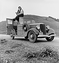 Dorothea Lange atop automobile in California.jpg