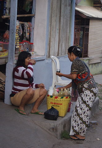 Jamu - Travelling Mbok Jamu selling jamu gendong attending to her customer