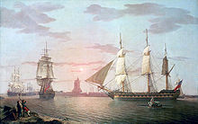In front of a setting sun, three sailing ships make their way out of a harbour with their lower sails set. A rowing boat is heading towards the nearest ship and two men watch the scene from the foreground.