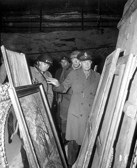 Dwight D. Eisenhower (right) inspects stolen artwork in a salt mine in Merkers, accompanied by Omar Bradley (left) and George S. Patton (center) Eisenhower, Bradley and Patton inspect looted art HD-SN-99-02758.JPEG