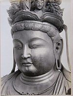 Portrait of a statue in three-quarter view with a full face and elongated earlobes. Small faces are located on top of its head.