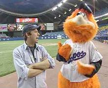 Youppi!, a big, bright orange furry mascot, interacts with a fan inside Montreal Olympic Stadium.