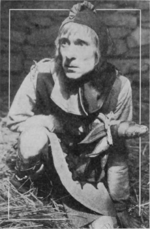 A man dressed as a fool crouches on a straw covered floor with a rough stone wall behind him. He holds a mock scepter in his right hand.