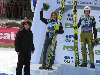 FIS Ski Flying World Championships 2010 - Winner Simon Ammann and second Gregor Schlierenzauer on the podium, bouquets presented by Slovenian Defence Minister Ljubica Jelušič