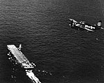 FM-2 Wildcat of VC-93 in flight over USS Petrof Bay (CVE-80) off Okinawa, in 1945.jpg