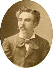 young man in semi profile, with luxuriant moustache and longish dark hair