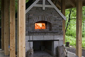 Wood-fired oven - A masonry wood-fired oven, during the firing (heating) stage.
