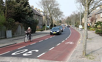 Roads in the Netherlands - A traffic-calmed street with wide advisory cycle lanes (red) that motorists may use to pass oncoming cars. Drivers must use them safely though and not crowd out the cyclists.