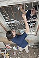 Flickr - Official U.S. Navy Imagery - A Navy officer helps paint a window grate..jpg