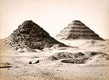 Two pyramids engulfed by the desert sand.