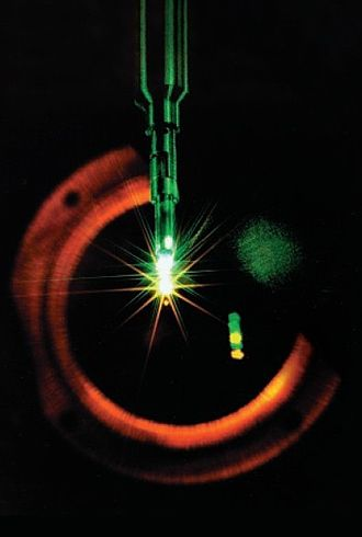 "Nova (laser) - Fusion target implosion on Nova. The green coloring of the target holder is due to the leftover laser light that was upconverted only ""half way"" to UV, stopping at green. The optics are arranged to focus this light ""short"" of the target, and here it strikes the holder. A small amount of IR light is also leftover, but this cannot be seen in this visible-light photograph. An estimate of the size of the implosion can be made by comparing the size of the target holder here with the image above."