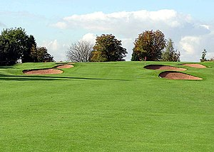 Greenskeeper - Bunkers at Filton Golf Club, Bristol, England. Greenskeepers edge the grass around the sand bunkers, and keep the sand raked smooth. Greens are fertilized for color and health.