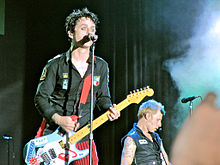 A man with black hair wearing a black button-up shirt and red pinstriped pants is singing into a microphone and playing a blue and white guitar.  Behind him in the bottom-right corner, a blonde man in a black shirt is also performing.