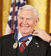A man with white hair dressed in a black suit, wearing the Presidential Medal of Freedom