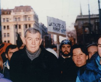 "Živorad Kovačević - Živorad and Margita Kovačević walking with students in Belgrade in 1997. The sign behind them says ""Walk with us."""