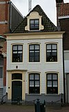 foto van Pand met gepleisterde rechte gevel, verticaal verdeeld door blokpilasters en voorzien van een lijst met panelen, omlijste dakkapel