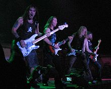 A color photograph of members of the band Iron Maiden on stage with guitars