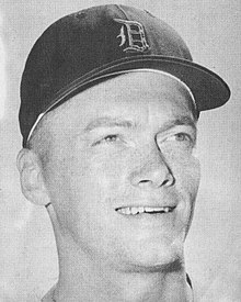 "A black-and-white headshot of a smiling man wearing a baseball cap with an Old English ""D"" on the face"