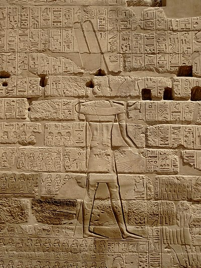 The Triumphal Relief of Shoshenq I near the Bubastite Portal at Karnak, depicting the god Amun-Re receiving a list of cities and villages conquered by the king in his Near Eastern military campaigns. Karnak Tempel 19.jpg