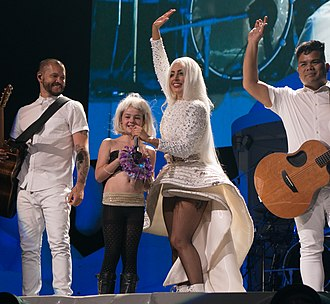 """Gypsy (Lady Gaga song) - Gaga, surrounded by her guitarists and an audience member brought on stage, performs """"Gypsy"""" on the ArtRave: The Artpop Ball tour, 2014"""