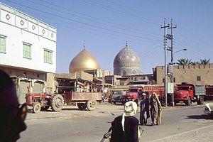 Samarra - Men walk down a street in Samarra in 1970. Al-Askari Shrine is in the background.