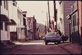 MAN WASHING HIS CAR WHILE A YOUNGSTER LOOKS ON IN AN OLDER WELL-MAINTAINED ETHNIC COMMUNITY ON THE SOUTH SIDE. THE... - NARA - 557288.tif
