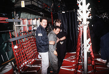 Gen. Manuel Noriega is escorted onto a U.S. Ai...