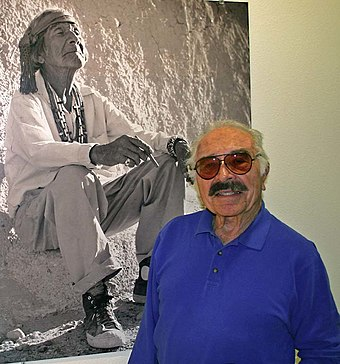 "Lee Marmon (Laguna Pueblo), next to his most famous photograph, ""White Man's Moccasins"" Marmon Publicity Photo for Web.jpg"