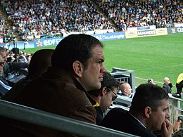 Photo de Martin Johnson assis dans les tribunes de l'Adams Park.