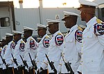 Members of the Haitian National Police Force marching band stand at parade.jpg