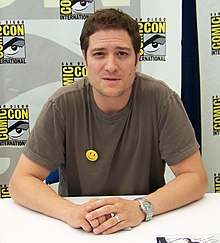 A man in his 30s, sitting at a San Diego Comic-Con International signing desk.