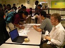 Twee jonge blanke mannen zitten aan een tafel met verschillende tiener Afro-Amerikaanse studenten eromheen, en een tekent er een papier op.  Ook op tafel ligt een laptop.