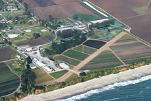 airstrip and buildings on coast in farm fields