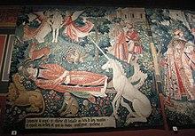 tapisserie ancienne et colorée de rouge, vert, bleu et blanc: un homme est couché dans un jardin et entouré notamment d'une licorne assise, d'un singe, d'un lion, d'un cerf et d'un porc-épic.