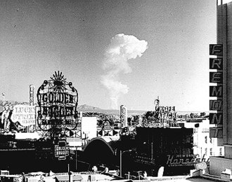 Las Vegas - This view of downtown Las Vegas shows a mushroom cloud in the background. Scenes such as this were typical during the 1950s. From 1951 to 1962 the government conducted 100 atmospheric tests at the nearby Nevada Test Site.