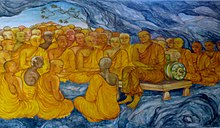 Mural painting with many monks sitting in a cave, one of them seated on a bench
