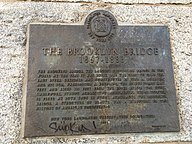 A plaque that certifies the Brooklyn Bridge as a New York City designated landmark