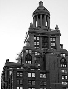 A high rise building with many tiers and a ten-columned cupola topping it.